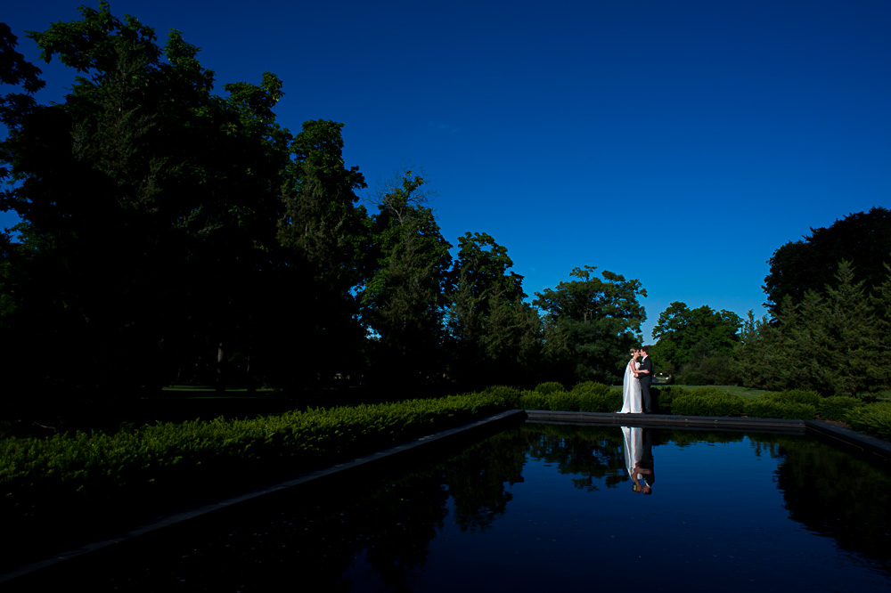 Wedding portrait in front of a reflective pool.