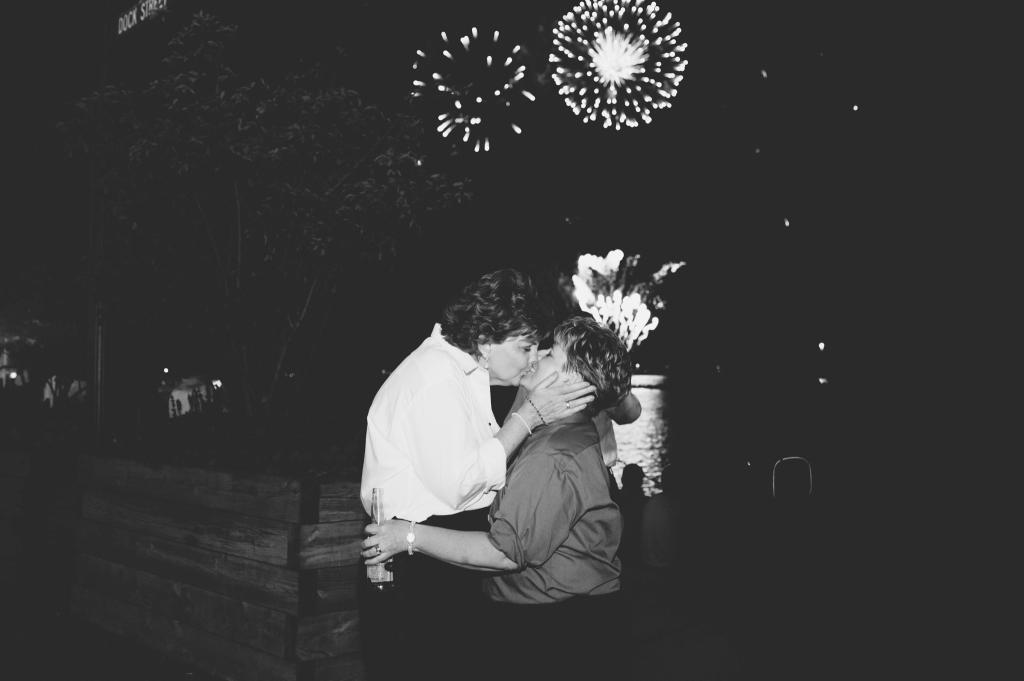 Black and white photo of two brides kissing with fireworks in the background.